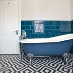 Image: Blue-tiled main bathroom with slipper bath and geometric flooring